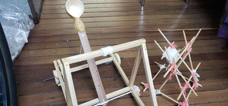 Imagem mostra uma catapulta feita com barbantes e tiras de madeira