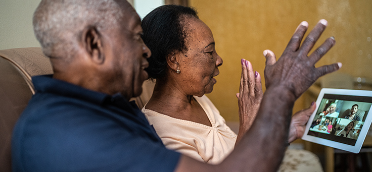 Imagem mostra um casal de idosos olhando para a tela de um tablet