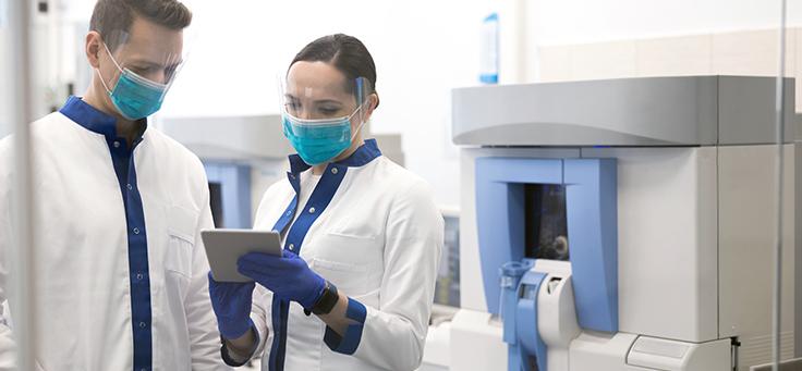 Imagem mostra um homem e uma mulher utilizando avental branco, luvas e máscara de proteção dentro de um laboratório