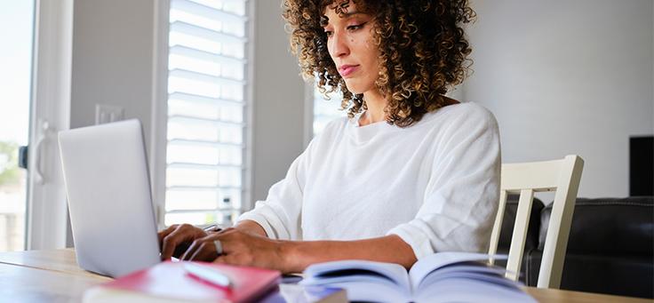 Imagem mostra mulher de blusa branca digitando em um notebook. Na frente dela há um livro aberto.