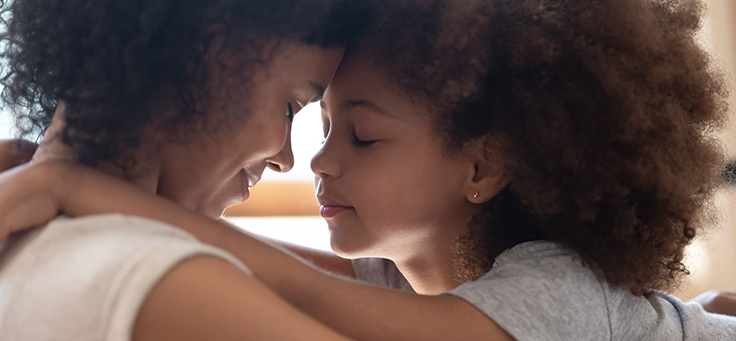 Imagem de mãe e filha se abraçando frente a frente com os olhos fechados e as testas juntas uma da outra