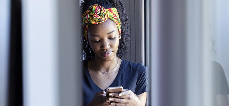 Imagem mostra uma jovem olhando para o celular