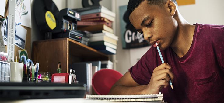 Imagem mostra um jovem olhando para um caderno e segurando um lápis