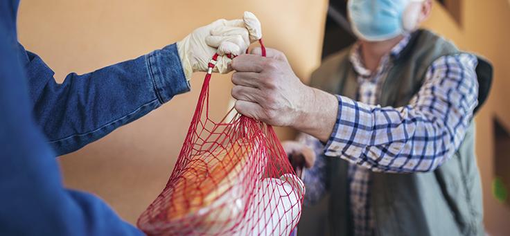 Imagem mostra um homem de máscara pegando uma sacola das mãos de outra pessoa usando luvas descartáveis