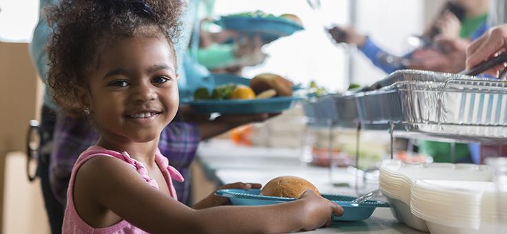 Imagem mostra uma criança sorrindo, segurado um prato com um pão