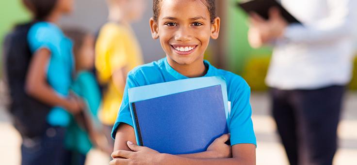 Imagem de uma criança de camiseta azul sorrindo enquanto segura alguns papeis azuis em suas mãos