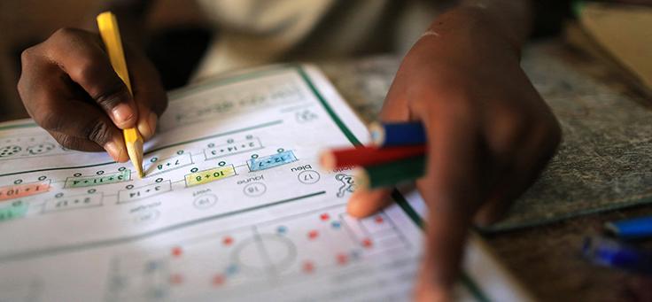 Imagem mostra duas mãos em destaque segurando alguns lápis coloridos e pintando uma folha de papel com alguns escritos
