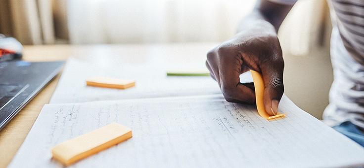Na imagem há uma mão em destaque colando um post-it em uma folha de papel