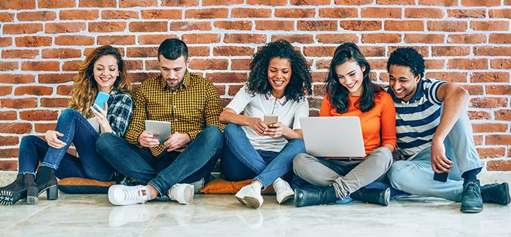 Na imagem três jovens estão sentados ao chão e compartilhando a tela de um notebook para ilustrar matéria sobre o lançamento do novo site do Pense Grande.