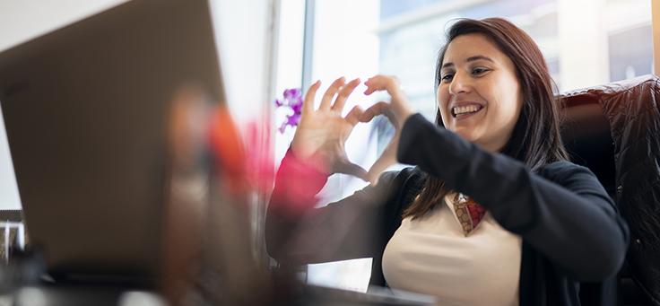 Mulher está sorrindo e olhando para tela do computador enquanto faz sinal de coração com as duas mãos. Imagem ilustra pauta sobre como manter o engajamento e a solidariedade em programas de voluntariado corporativo.