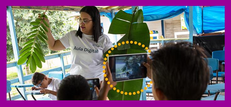 A foto mostra uma formadora do Projeto Aula Digital, que usa uma camiseta com o nome do programa, mostrando uma planta que está em suas mãos para um grupo de alunos. Um deles, segura um tablet com a câmera apontada na direção dela.