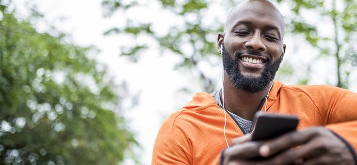 A imagem mostra um homem negro sorrindo, de blusa laranja, usando fones de ouvido enquanto olha para a tela de um celular. Ao fundo dele se vê algumas árvores.