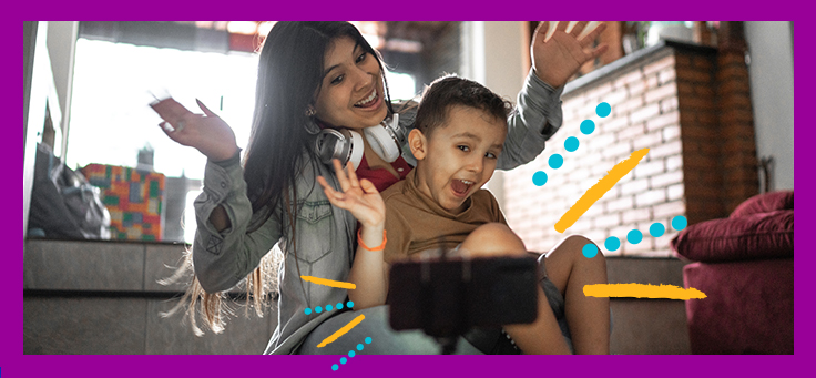A imagem mostra uma mãe sentada no chão com o filho no colo. Ambos estão sorrindo e com as mãos levantadas enquanto olham para a tela do celular que está apoiado em um suporte em frente a eles.