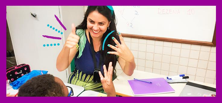 Imagem mostra educadora fazendo gesto da língua de sinais de frente para estudante em sala de aula. Ela veste vestido com desenhos em tons de azul e verde e tem um lenço azul amarrando os cabelos.
