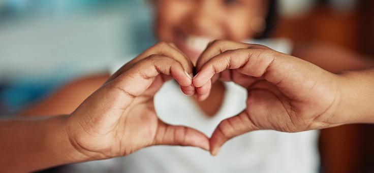 Imagem mostra em primeiro plano as mãos de uma menina fazendo gesto de coração para ilustrar pauta sobre como o voluntariado digital e a mobilização de ações pelo bem podem aprimorar habilidades na carreira profissional.