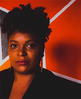 Foto de Magda Pereira de Souza, integrante do grupo Quem disse que eu não gosto de estudar?, que usou o pensamento computacional para criar um jogo relacionado à cultura afro-brasileira. Ela é uma mulher negra de cabelos enrolados, olha firme para a câmera e usa batom rosa e uma roupa preta.