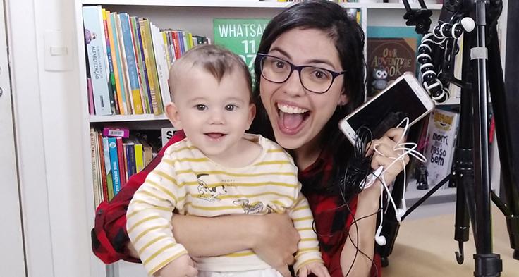 Lorena Carvalho, conhecida pelo canal Professora Coruja que foca em alfabetização e cultura digital, está segurando um bebê no colo e segurando um smartphone com a mão direita. Ao fundo há uma estante com livros.