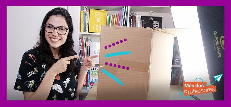 Lorena Carvalho, conhecida pelo canal Professora Coruja que foca em alfabetização e cultura digital, está apontando para uma caixa de papelão. Ela é uma mulher de 27 anos, com cabelos compridos e castanhos e está usando óculos.
