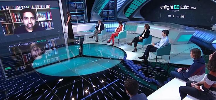 A imagem mostra palco de uma das conferências do enlightED 2020, conferência que mostra tendências da educação global. Há quatro pessoas sentadas em cadeiras em semicírculo e um homem sendo entrevistado, aparecendo em um telão no centro.