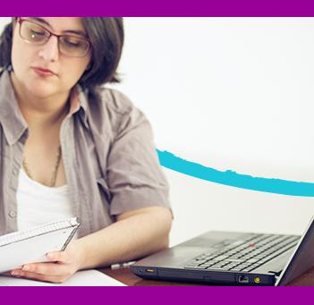 A imagem mostra uma mulher sentada atrás de uma mesa, fazendo anotações em um caderno. Sobre a mesa há um notebook, um estojo e outros materiais como agenda e caderneta.