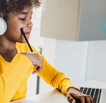 A imagem mostra uma criança usando fones de ouvido enquanto olha para a tela de um notebook para ilustrar pauta sobre a Hora do Código e a promoção da cultura digital. Ela é negra, tem cabelos encaracolados e usa uma blusa amarela.