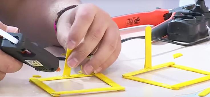 A imagem mostra a mão de uma pessoa que está usando cola quente para fazer uma forma geométrica durante o Movimento Inova, , evento que abordou temas como pensamento computacional e robótica.