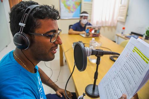 Imagem mostra um homem de camiseta azul em uma sala com fones de ouvido, falando ao microfone e lendo um papel. Ao fundo da mesa se vê um rapaz de máscara de proteção, mexendo em um notebook.