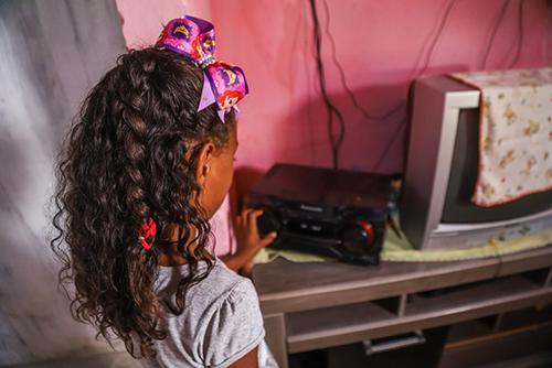 A imagem mostra uma menina de costas mexendo em um rádio sobre uma mesa.