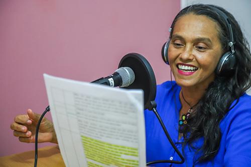 Imagem mostra uma mulher de camiseta azul e fones de ouvido lendo um papel enquanto fala ao microfone