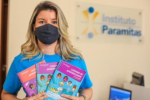 Imagem mostra uma mulher de camisera azul e máscara de proteção preta segurando vários cadernos de aprendizagem