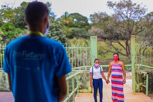 Imagem mostra uma mulher grávida de mãos dadas com uma menina de uniforme escolar e mochila, em frente a um portão aberto. Há um rapaz de costas, vestindo um camiseta azul, olhando para elas.