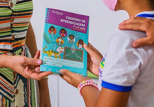 A imagem mostra uma criança recebendo um dos cadernos de apredizagem nas mãos de uma pessoa