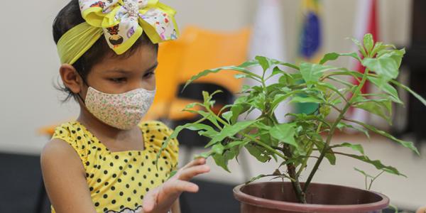 Criança usando máscara segura muda de planta em atividade na Associação Colorindo a Vida durante a Semana dos Voluntários.