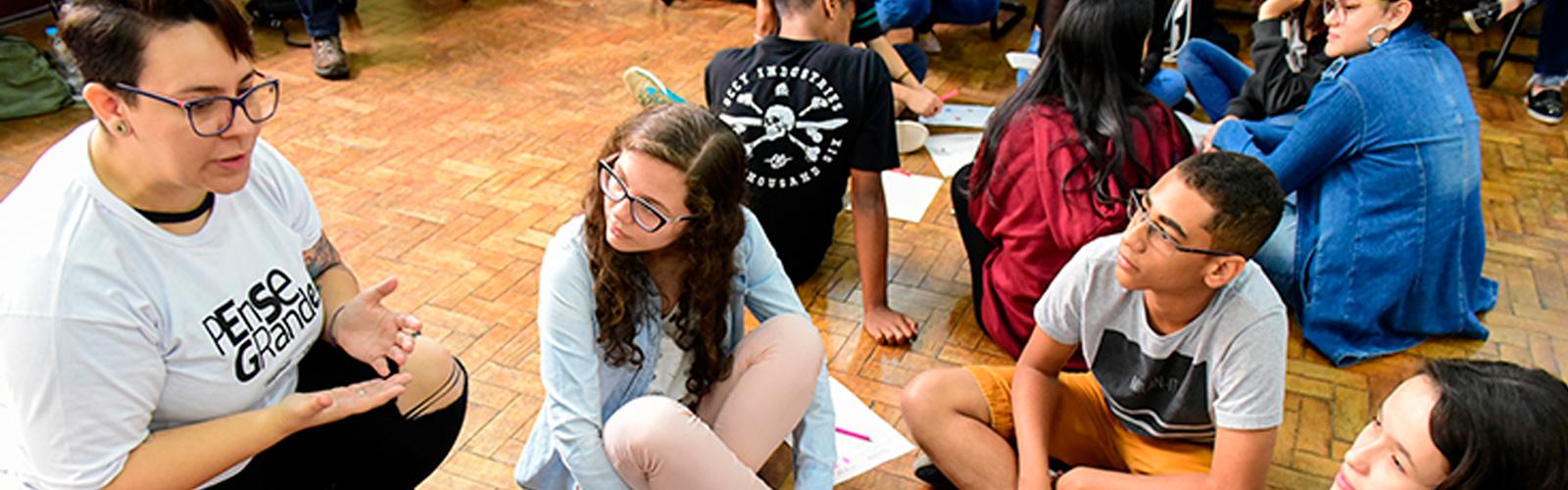 Jovens e formadores do programa Pense Grande estão sentados no chão em grupos, formando círculos.