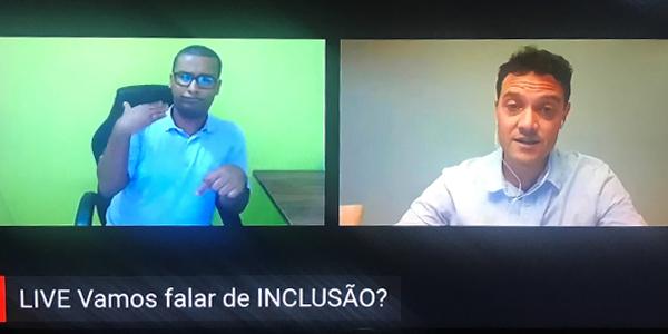 Educador Igor Zucchi está falando em live da Associação Cararinense para a Integração do Cego durante a Semana dos Voluntários. Ele divide a tela com um intérprete de Libras.