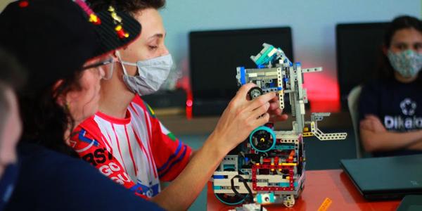 Estudante da Associação Beneficente Dikaion aparece em destaque, usando máscara facial, e manuseando um dispositivo durante oficina de robótica na Semana dos Voluntários.