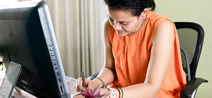 Na imagem uma mulher está escrevendo em frente a um computador para ilustrar o papel dos curadores da plataforma Escola Digital, que fortalece a formação de professores.