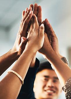 Para simbolizar as ações de voluntariado da Semana dos Voluntários, a imagem traz um grupo de cinco pessoas unindo suas mãos no ar.