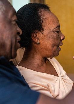 Para simbolizar as ações de voluntariado da Semana dos Voluntários, a imagem traz a imagem de uma senhora e um senhor que estão utilizando um dispositivo para uma chamada a distância.