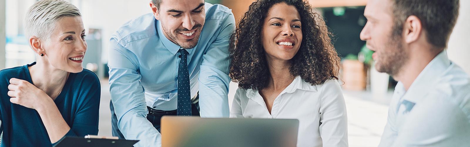 grupo de colabadores de uma empresa sorriem durante uma reunião