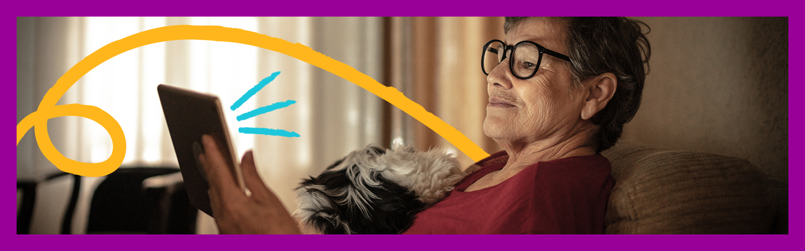 A imagem mostra uma senhora sentanda em um sofá com um cachorro no colo olhando para a tela de um tablet.
