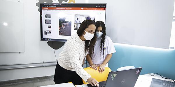 Imagem apresenta duas pessoas olhando para um notebook. Ao fundo se vê um projetor.