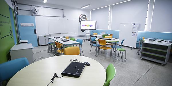 Foto traz uma visão geral do espaço maker. Há três mesas com cadeiras coloridas, um projetor e lousas.