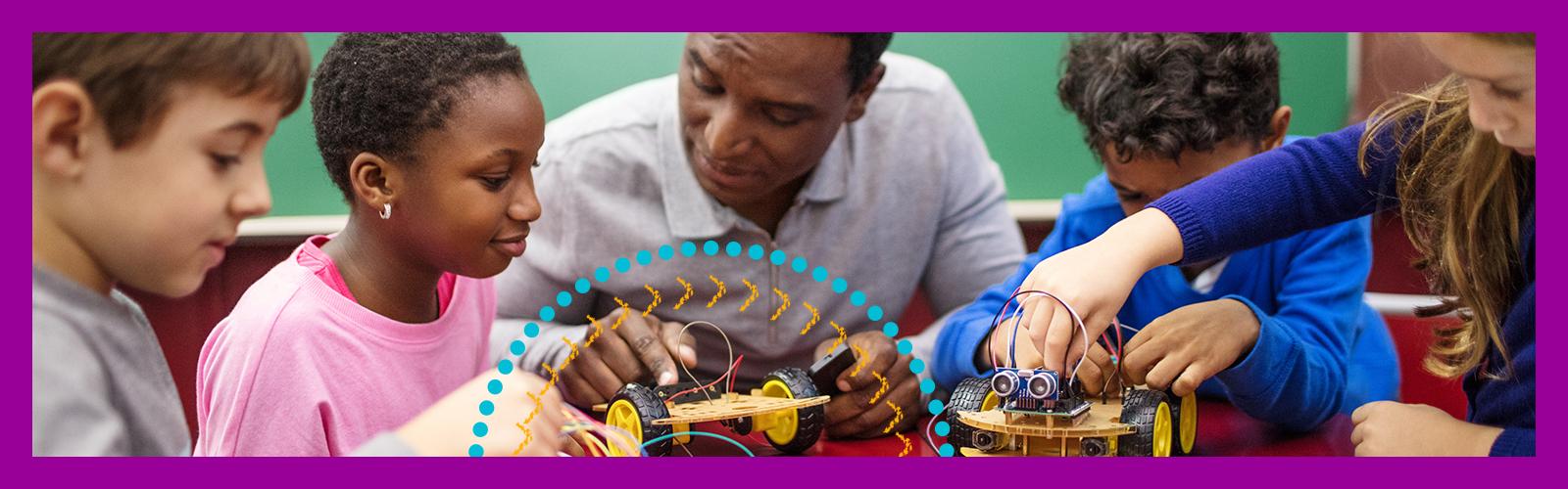 Imagem mostra professor montando protótipos durante uma aula de robótica. Ele é um homem negro de cabelos curtos e enrolados e está sentado a uma mesa rodeada por estudantes que aparentam ter em torno de 10 anos.