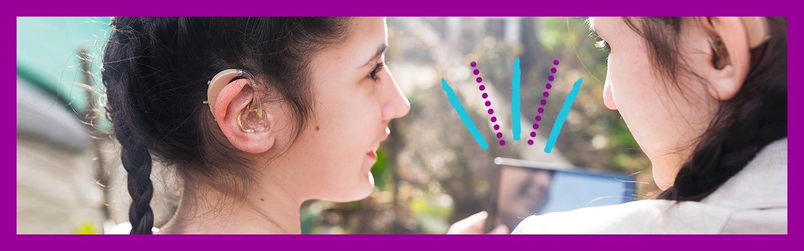 Imagem mostra uma menina com aparelho de surdez ao lado de uma mulher que segura um tablet nas mãos