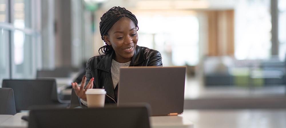 Imagem mostra uma jovem sentada atrás de uma mesa com um notebook a frente dela e um copo de café descartável ao lado