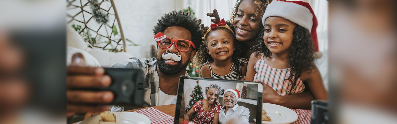 Imagem mostra pai, mãe e filhas fazendo chamada com avós durante o Natal. Os avós aparecem em uma tela de tablet e todos os usam adereços natalinos, como gorro de Papai Noel.
