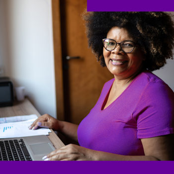 Imagem mostra uma senhora negra sentada em frente a uma mesa com as mãos sobre um notebook. Ela usa uma camiseta púrpura, óculos de grau e está sorrindo.