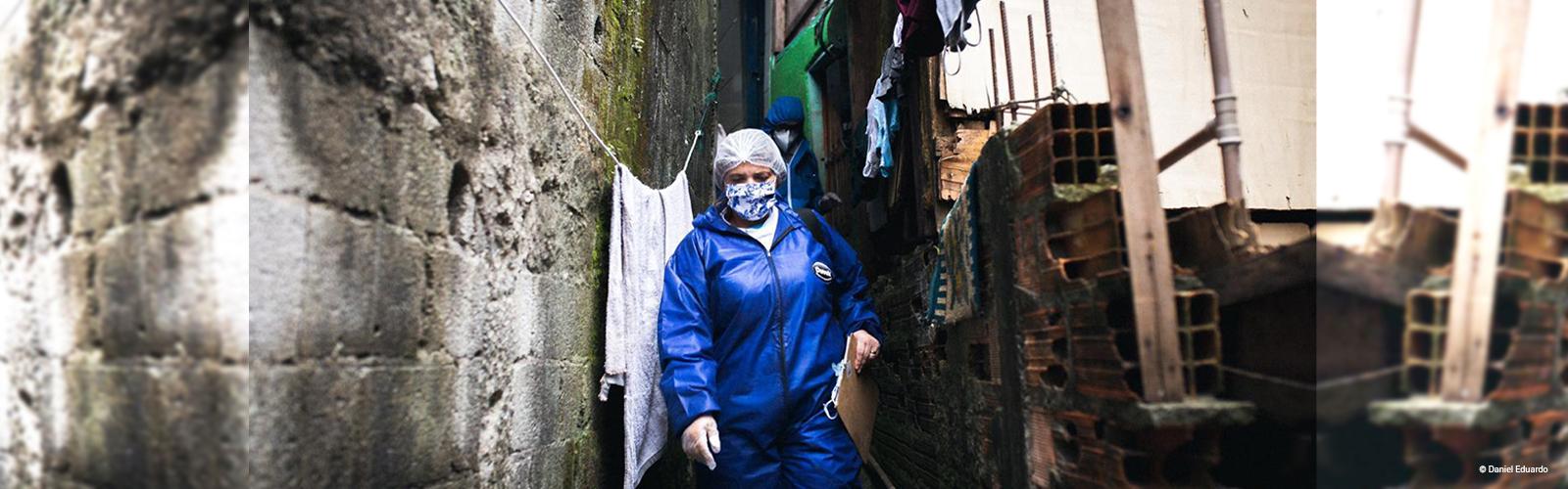 Imagem mostra uma mulher de máscara de proteção e agasalho azul andando pela comunidade de Paraisópolis