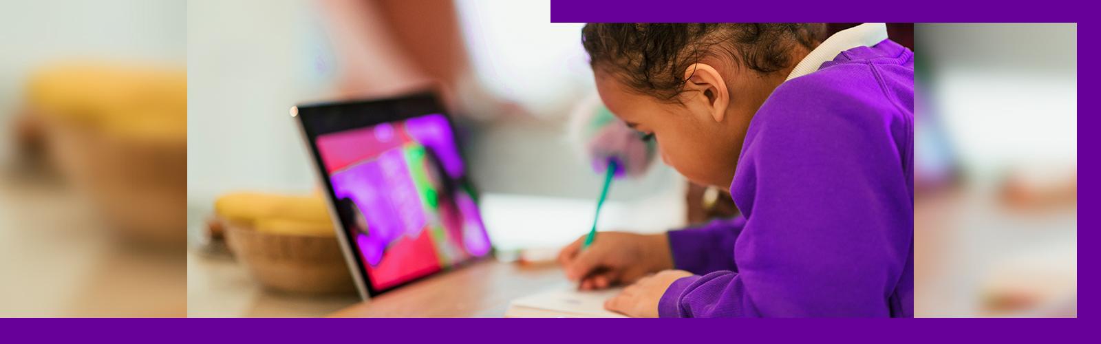 Imagem mostra menina escrevendo em um caderno. Na frente dela se vê um tablet.